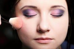 Cara del maquillaje que aplica colorete del colorete Imágenes de archivo libres de regalías