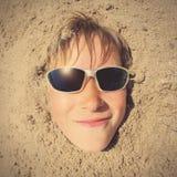 Cara del niño en la arena Imágenes de archivo libres de regalías