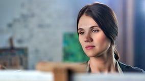 Cara del primer de la imagen femenina joven europea hermosa del dibujo del pintor usando las pinturas y cepillo almacen de video