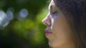 Cara del primer de la mujer con los cerrado-ojos, meditación en parque, relajación al aire libre metrajes