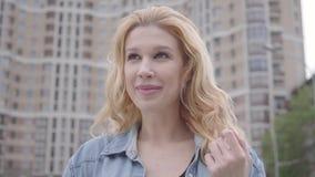 Cara del primer de la mujer rubia confiada bastante sonriente que habla con el interlocutor irreconocible delante del rascacielos metrajes
