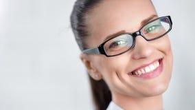 Cara del primer de los vidrios que llevan hermosos sonrientes de la mujer de negocios aislados en el estudio blanco almacen de video