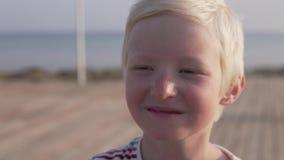 Cara del primer de un muchacho rubio hermoso el beb? es sonrisa linda almacen de metraje de vídeo