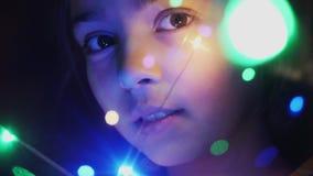 Cara del primer de una muchacha a través de luces luminosas almacen de metraje de vídeo