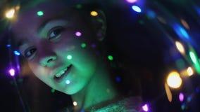 Cara del primer de una muchacha a través de luces luminosas almacen de video