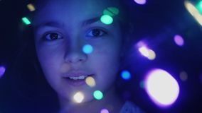 Cara del primer de una muchacha a través de luces luminosas metrajes