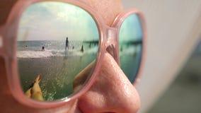 Cara del primer de una mujer feliz en gafas de sol La playa con la gente de reclinación se refleja en los vidrios 4k, lento almacen de metraje de vídeo