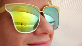 Cara del primer de una mujer feliz en gafas de sol La playa con la gente de reclinación se refleja en los vidrios 4k, lento almacen de video