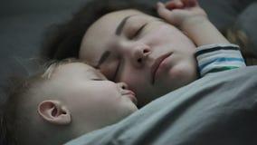 Cara del primer de una mujer joven y de un niño pequeño que duermen en cama almacen de metraje de vídeo