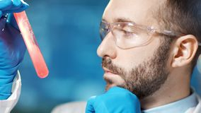 Cara del primer del doctor químico de sexo masculino confiado que mira en la extensión de sangre roja en cubilete metrajes