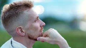 Cara del primer del hombre relajado que piensa tocando la barba que mira la naturaleza asombrosa que disfruta de soledad almacen de video