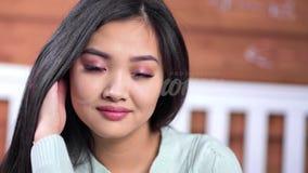 Cara del primer del modelo femenino asiático joven bastante sonriente que lleva el maquillaje natural que mira la cámara almacen de metraje de vídeo
