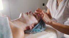 Cara del ` s del cliente de la limpieza del Cosmetologist con la loción especial después del procedimiento cosmético metrajes