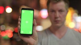 Cara del teléfono turístico feliz joven de la demostración del hombre con la pantalla verde en Chinatown en la noche almacen de metraje de vídeo