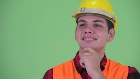 Cara del trabajador de construcción étnico multi joven feliz del hombre que piensa y que mira para arriba almacen de video