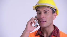 Cara del trabajador de construcci?n hisp?nico feliz joven del hombre que habla en el tel?fono almacen de metraje de vídeo