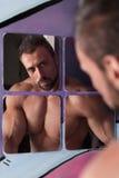 Cara descamisado considerável da lavagem do homem do músculo no espelho do banheiro Fotos de Stock