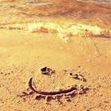 Cara divertida de la sonrisa dibujada en la arena mojada de la playa Imagenes de archivo