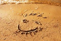 Cara divertida de la sonrisa dibujada en la arena mojada de la playa Imagen de archivo libre de regalías