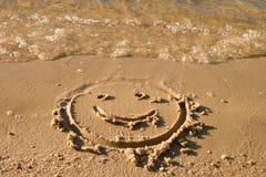 Cara divertida de la sonrisa en la arena mojada cerca del mar Fotografía de archivo libre de regalías