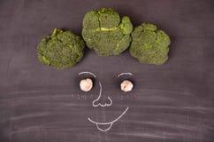 Cara divertida de verduras en la tierra negra Foto de archivo libre de regalías