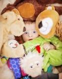Cara do bebê nos brinquedos Fotografia de Stock Royalty Free