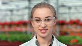 Cara do close-up do biólogo agrícola fêmea de sorriso nos vidros que aprecia a ruptura que olha a câmera vídeos de arquivo