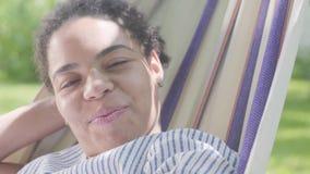 Cara do close-up da mulher afro-americano feliz adorável que encontra-se na rede, relaxando no jardim Lazer fora filme