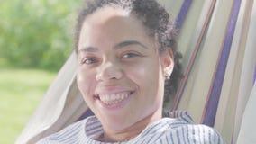Cara do close-up da mulher afro-americano feliz bonito que encontra-se na rede, relaxando no jardim Lazer fora filme