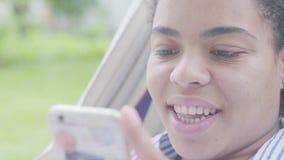 Cara do close-up da mulher afro-americano feliz que encontra-se na rede, relaxando no jardim, texting em seu telefone celular filme