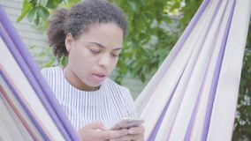 Cara do close-up da mulher afro-americano nova que senta-se na rede, relaxando no jardim, texting no telefone celular filme