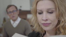 Cara do close up da mulher loura bonita que lê alto o livro no primeiro plano quando homem modestamente vestido que olha vídeos de arquivo
