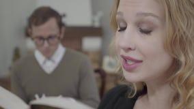 Cara do close-up da mulher loura bonita que lê alto o livro no primeiro plano quando homem modestamente vestido que olha filme