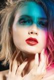 A cara do close-up de uma menina loura nova bonita com bordos vermelhos e sua cara são cobertas com as sombras coloridas de mult fotografia de stock royalty free