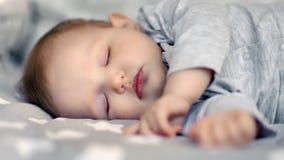 Cara do close-up do sono pouca criança infantil bonito que encontra-se com olhos fechados filme