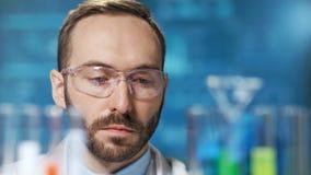 Cara do close-up do trabalhador químico masculino pensativo que olha na taça com a amostra líquida colorida filme