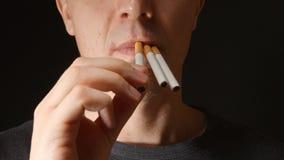 Cara do homem adulto novo que toma alguns cigarros em sua boca filme