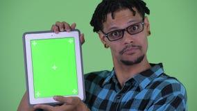 Cara do homem africano novo feliz do moderno que fala ao mostrar a tabuleta digital video estoque