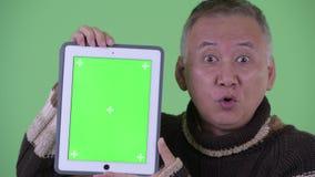 Cara do homem japonês maduro feliz que fala ao mostrar a tabuleta digital filme