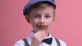 Cara do menino do guloso coberta no chocolate que olha a câmera, comendo demais o açúcar filme