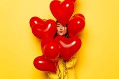 Cara do ` s da mulher que esconde entre balões vermelhos no fundo amarelo Imagens de Stock