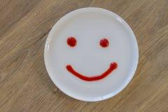 Cara do smiley da fonte do tomate na placa branca Foto de Stock