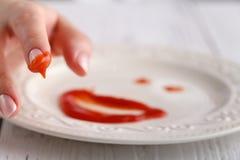 Cara do smiley da fonte do tomate na placa branca sobre o fundo de madeira Imagens de Stock Royalty Free