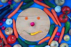 Cara do smiley feita dos vegetais entre vegetais coloridos Imagens de Stock