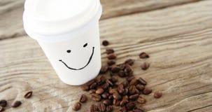 Cara do smiley no copo descartável com os feijões de café no saco filme
