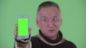 Cara do telefone japonês maduro feliz da exibição do homem vídeos de arquivo