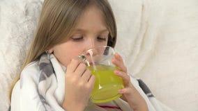 A cara doente da criança que bebe drogas, retrato doente triste da menina toma o sofá do medicamento video estoque