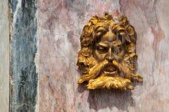 Cara dourada da fonte de Netuno na parede de mármore Imagem de Stock