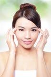 A cara e o dedo do sorriso da mulher apontam aos olhos Fotografia de Stock Royalty Free