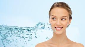 Cara e ombros da mulher sobre o respingo da água Fotografia de Stock